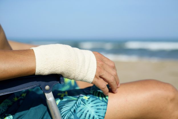 closeup of a young caucasian man in swimsuit sitting in a deck chair on the beach with a bandage in his wrist